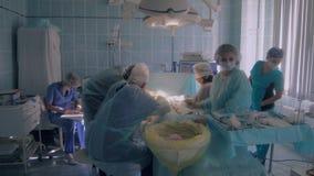 Ιατρική ομάδα στο λειτουργούν δωμάτιο που ολοκληρώνει τη χειρουργική επέμβαση απόθεμα βίντεο