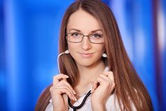 Ιατρική Ο ελκυστικός θηλυκός γιατρός στο μπροστινό, μπλε υπόβαθρο, όμορφη γυναίκα, νέος γιατρός, αναμειγνύει Στοκ εικόνα με δικαίωμα ελεύθερης χρήσης