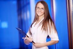 Ιατρική Ο ελκυστικός θηλυκός γιατρός στο μπροστινό, μπλε υπόβαθρο, όμορφη γυναίκα, νέος γιατρός, αναμειγνύει Στοκ εικόνες με δικαίωμα ελεύθερης χρήσης