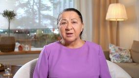 ιατρική on-line Ηλικιωμένη γυναίκα που συσκέπτεται με το γιατρό της που χρησιμοποιεί την τηλεοπτική συνομιλία στο σπίτι απόθεμα βίντεο