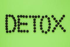 """Ιατρικός ενεργοποιημένος ξυλάνθρακας υπό μορφή επιγραφής """"detox σε ένα πράσινο υπόβαθρο E στοκ εικόνες"""
