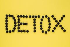 """Ιατρικός ενεργοποιημένος ξυλάνθρακας υπό μορφή επιγραφής """"detox σε ένα κίτρινο υπόβαθρο E στοκ εικόνες"""