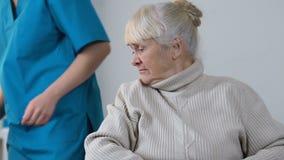 Ιατρικός εργαζόμενος που κινεί το κατά μέρος λυπημένο ηλικίας άτομα με ειδικές ανάγκες θηλυκό στην αναπηρική καρέκλα, μοναξιά απόθεμα βίντεο