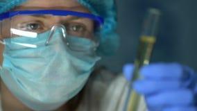 Ιατρικός εργαζόμενος που κρατά το κίτρινο υγρό δείγμα στο σωλήνα δοκι φιλμ μικρού μήκους