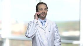 Ιατρικός εργαζόμενος που μιλά στο τηλέφωνο κυττάρων απόθεμα βίντεο