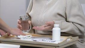 Ιατρικός εργαζόμενος που παίρνει το ποτήρι του νερού από τη μόνη ηλικιωμένη κυρία στη ιδιωτική κλινική φιλμ μικρού μήκους