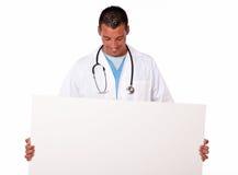 Ιατρικός νέος γιατρός που κρατά μια άσπρη αφίσσα Στοκ φωτογραφίες με δικαίωμα ελεύθερης χρήσης