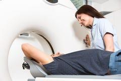 Ιατρικός τεχνικός βοηθός που προετοιμάζει την ανίχνευση της σπονδυλικής στήλης με το CT Στοκ Εικόνες