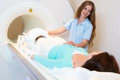Ιατρικός τεχνικός βοηθός που προετοιμάζει την ανίχνευση του γονάτου με MRI Στοκ Φωτογραφία