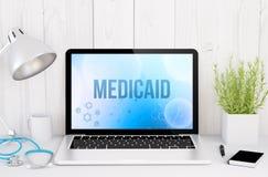 ιατρικός υπολογιστής γραφείου με το medicaid στην οθόνη στοκ φωτογραφία