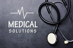 Ιατρικό κείμενο λύσεων στον πίνακα με το στηθοσκόπιο και το ποσοστό κτύπου της καρδιάς στοκ φωτογραφία