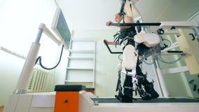 ιατρικό ρομπότ Ιατρικό δωμάτιο κατάρτισης με έναν αρσενικό ασθενή που ασκεί σε έναν προσομοιωτή περπατήματος απόθεμα βίντεο
