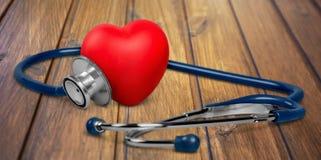 Ιατρικό στηθοσκόπιο με την πλαστική καρδιά σε ξύλινο στοκ φωτογραφίες