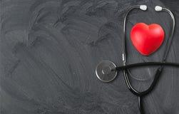 Ιατρικό στηθοσκόπιο με την πλαστική καρδιά σε ξύλινο στοκ φωτογραφία με δικαίωμα ελεύθερης χρήσης