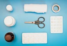 Ιατρικό σύνολο: ψαλίδι, επίδεσμοι, χάπια σε ένα μπλε υπόβαθρο Στοκ Φωτογραφίες