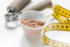διατροφή για το workout με την πρωτεϊνική σκόνη κοκτέιλ, την ταινία μέτρου και τους φραγμούς στο άσπρο υπόβαθρο στοκ εικόνα