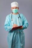 Ιατρός με τη μάσκα στηθοσκοπίων και προσώπου που κρατά μια μάνδρα και Στοκ εικόνα με δικαίωμα ελεύθερης χρήσης