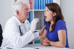 Ιατρός παθολόγος που εξετάζει το λαιμό Στοκ εικόνες με δικαίωμα ελεύθερης χρήσης