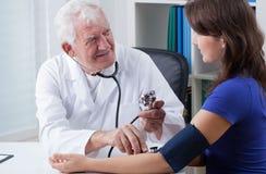 Ιατρός παθολόγος που παίρνει τη πίεση του αίματος Στοκ φωτογραφία με δικαίωμα ελεύθερης χρήσης