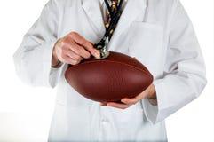 Ιατρός που ελέγχει την υγεία του ποδοσφαίρου στο άσπρο υπόβαθρο στοκ φωτογραφίες