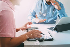 Ιατρός χρησιμοποιώντας το κινητό τηλέφωνο και συμβουλευτικός το ελαφρύ κτύπημα επιχειρηματιών Στοκ Εικόνες