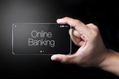 Διαφανές smartphone με το σε απευθείας σύνδεση τραπεζικό εικονίδιο στο σκοτεινό backgrou Στοκ Εικόνες