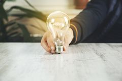 Ιδέα ή λάμπα φωτός χεριών ατόμων στοκ εικόνες