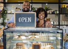 Ιδιοκτήτες καφέδων κέικ με το ανοικτό σημάδι στοκ εικόνες