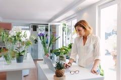 Ιδιοκτήτης μαγαζιό λουλουδιών που εργάζεται στο lap-top Στοκ φωτογραφία με δικαίωμα ελεύθερης χρήσης