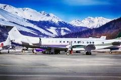 Ιδιωτικά αεριωθούμενα αεροπλάνα, αεροπλάνα και ελικόπτερα στον αερολιμένα του ST Moritz Ελβετία στα όρη Στοκ Φωτογραφία
