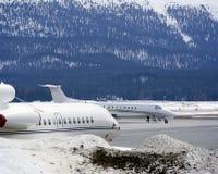 Ιδιωτικά αεριωθούμενα αεροπλάνα, αεροπλάνα και στο χιονισμένο τοπίο της Ελβετίας Στοκ εικόνα με δικαίωμα ελεύθερης χρήσης