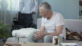Ιδιωτική κλινική Παρεμποδισμένη συνεδρίαση ατόμων στον καναπέ Αρσενική φέρνοντας αναπηρική καρέκλα νοσοκόμων απόθεμα βίντεο