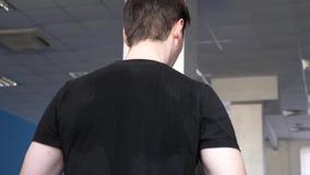 Ιδρωμένα πίσω άτομα στην κινηματογράφηση σε πρώτο πλάνο μπλουζών άτομο λεσχών ικανότητας που συμμετέχεται στο περπάτημα ενισχύοντ απόθεμα βίντεο