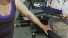 Ιδρωμένο παχύ θηλυκό που ασκεί treadmill, γιατρός που παίρνει τα αποτελέσματα, αποκατάσταση απόθεμα βίντεο