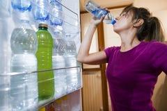 Ιδρωμένο πόσιμο νερό γυναικών που βλέπει από μέσα από το ψυγείο στοκ εικόνες με δικαίωμα ελεύθερης χρήσης