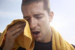 Ιδρώνοντας νεαρός άνδρας με μια πετσέτα στοκ φωτογραφία