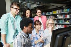 Διεθνείς σπουδαστές με τους υπολογιστές στη βιβλιοθήκη Στοκ Εικόνες
