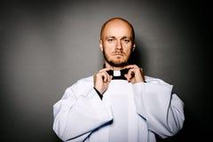 Ιερέας στο άσπρο στιχάριο που διορθώνει το περιλαίμιό του στοκ εικόνα
