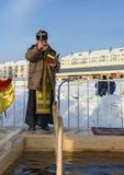 Ιερέας consecrates η τρύπα πάγου την ημέρα Epiphany Ρωσία Στοκ Φωτογραφία