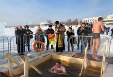 Ιερέας consecrates η τρύπα πάγου την ημέρα Epiphany Ρωσία Στοκ Εικόνες