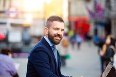 Διευθυντής Hipster που εργάζεται στο lap-top στο ηλιόλουστο τσίρκο Piccadilly, Lo Στοκ Εικόνα