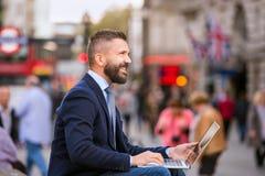 Διευθυντής Hipster που εργάζεται στο lap-top στο ηλιόλουστο τσίρκο Piccadilly, Lo Στοκ εικόνες με δικαίωμα ελεύθερης χρήσης