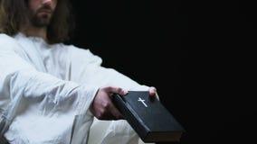 Ιησούς στην τήβεννο που παρουσιάζει ιερή Βίβλο στη κάμερα, την πίστη και την πεποίθηση, σκοτεινό υπόβαθρο απόθεμα βίντεο