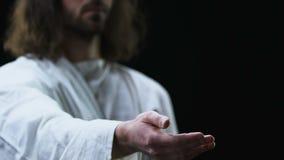 Ιησούς Χριστός που φθάνει έξω στο χέρι του στο σκοτεινό κλίμα, που βοηθά τους ανθρώπους απόθεμα βίντεο