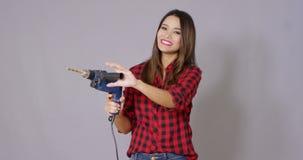 Ικανή ελκυστική νέα γυναίκα που κρατά ένα τρυπάνι απόθεμα βίντεο