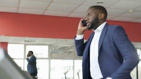 Ικανοποιημένη άσκηση χαμόγελου businessperson treadmill και ομιλία στο τηλέφωνο φιλμ μικρού μήκους