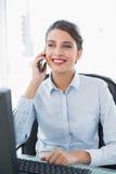 Ικανοποιημένη αριστοκρατική καφετιά μαλλιαρή επιχειρηματίας που κάνει ένα τηλεφώνημα Στοκ Φωτογραφίες