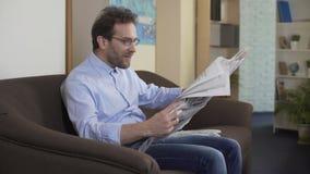 Ικανοποιημένη κύρια εφημερίδα ανάγνωσης, χαλαρωμένη συνεδρίαση προσώπων στον καναπέ, Τύπος απόθεμα βίντεο