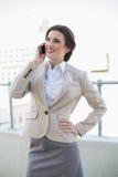 Ικανοποιημένη μοντέρνη καφετιά μαλλιαρή επιχειρηματίας που κάνει ένα τηλεφώνημα Στοκ φωτογραφίες με δικαίωμα ελεύθερης χρήσης