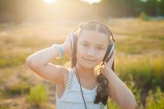 Ικανοποιημένη μουσική ακούσματος κοριτσιών με τα ακουστικά Στοκ εικόνες με δικαίωμα ελεύθερης χρήσης